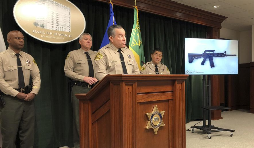 Los Angeles County Sheriff Alex Villanueva, at podium, talks about the arrest of a 13-year-old boy and the seizure of a rifle and ammunition after the teen threatened to shoot other students and staff at his Los Angeles-area middle school, at Sheriff's headquarters in downtown Los Angeles Friday, Nov. 22, 2019. Villanueva said deputies serving a search warrant at the boy's home Thursday discovered an AR-15-style gun, 100 rounds of ammunition, a list of names and a drawing of the school. Villanueva said the boy said he would carry out the shooting Friday at Animo Mae Jemison Charter Middle School in Willowbrook, an unincorporated county area near South Los Angeles. (AP Photo/Brian Melley)