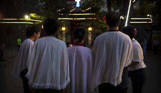 FILE - In this Sept. 22, 2018, file photo, members of the faithful gather before a Mass at the Cathedral of the Immaculate Conception, a government-sanctioned Catholic church in Beijing. A Chinese Catholic priest whose demotion was key to a now-stalled effort at reconciliation between China and the Vatican is being pressured to join the official Communist Party-controlled church organization, a fellow priest and Catholic news source said. (AP Photo/Mark Schiefelbein, File)