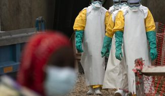 """FILE - In this Tuesday, July 16, 2019 file photo, health workers dressed in protective gear begin their shift at an Ebola treatment center in Beni, Congo DRC. The World Health Organization said Friday Nov. 22, 2019, there has been """"a very dangerous and alarming development"""" in efforts to end the Ebola outbreak in eastern Congo, warning that the eruption of violence may re-ignite the epidemic. (AP Photo/Jerome Delay, File)"""