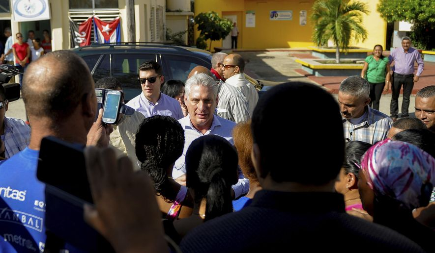 FILE - In this Nov. 14, 2019 file photo, Cuba's President Miguel Diaz-Canel, center, visits with residents after arriving in Caimanera, Cuba. A new decree approved by Diaz-Canel Oct. 8 and made public Monday, Nov. 18, 2019, says prosecutors can approve eavesdropping and surveillance of any form of communication, without consulting a judge as required in many other Latin American countries.  (AP Photo/Ismael Francisco, File)