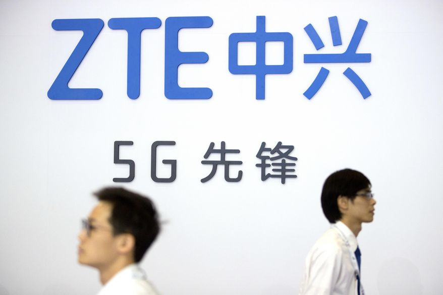 In this Sept. 26, 2018, file photo, visitors walk beneath the logo of Chinese technology firm ZTE at the PT Expo in Beijing. (AP Photo/Mark Schiefelbein, File)