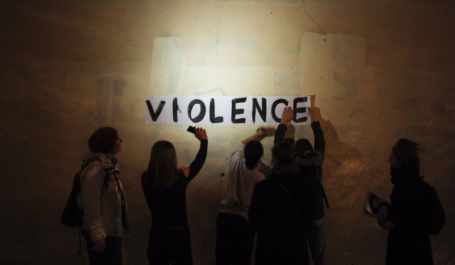"In this Oct. 31, 2019 photo, the word ""violence"" is pasted onto a wall by a group of women in a dark street in Paris. In Paris and cities across France, the signs are everywhere. ""Complaints ignored, women killed"" and ""She leaves him, he kills her,"" they read in black block letters pasted over stately municipal buildings. Under cover of night, activists have glued them to the walls to draw attention to domestic violence, a problem French President Emmanuel Macron has called ""France's shame."" (AP Photo/Kamil Zihnioglu)"