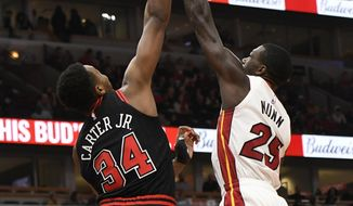 Miami Heat's Kendrick Nunn (25) goes up for a shot against Chicago Bulls' Wendall Carter Jr. (34) during the first half of an NBA basketball game Friday, Nov. 22, 2019, in Chicago. (AP Photo/Paul Beaty)