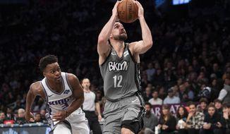 Brooklyn Nets guard Joe Harris (12) drives to the basket against Sacramento Kings guard Yogi Ferrell (3) during the second half of an NBA basketball game, Friday, Nov. 22, 2019, in New York. The Nets won 116-97. (AP Photo/Mary Altaffer)