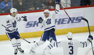 Toronto Maple Leafs left wing Pierre Engvall, center, has trouble celebrating his goal against the Arizona Coyotes as he loses his balance between Maple Leafs defensemen Morgan Rielly (44) and Justin Holl (3) during the second period of an NHL hockey game Thursday, Nov. 21, 2019, in Glendale, Ariz. (AP Photo/Ross D. Franklin)