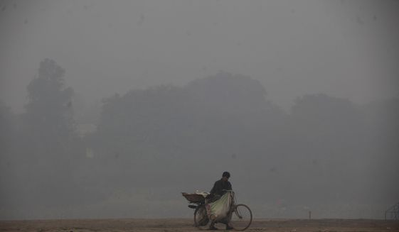 """A cyclist pushes his laden bike through smog, in Lahore, Pakistan, Thursday, Nov. 21, 2019. Amnesty International issues """"Urgent Action"""" saying every person in Lahore at risk. Heavy smog has enveloped many cities of Punjab province, causing highway accidents and respiratory problems, and forcing many residents to stay home. (AP Photo/K.M. Chaudary)"""