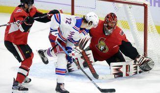Ottawa Senators goaltender Anders Nilsson (31) makes a glove save on New York Rangers center Filip Chytil (72) as Senators' Dylan DeMelo (2) defends during the third period of an NHL hockey game Friday, Nov. 22, 2019, in Ottawa, Ontario. (Sean Kilpatrick/The Canadian Press via AP)