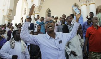 """Relatives of Somali Canadian peace activist Almaas Elman shout """"We need Justice"""" outside the Mosque of Islamic Solidarity where her funeral service was held, in the capital Mogadishu, Somalia Friday, Nov. 22, 2019. Preliminary investigations show Almaas Elman was killed by a stray bullet inside a heavily defended base near the international airport earlier this week in Mogadishu, the peacekeeping mission in Somalia said Friday. (AP Photo/Farah Abdi Warsameh)"""