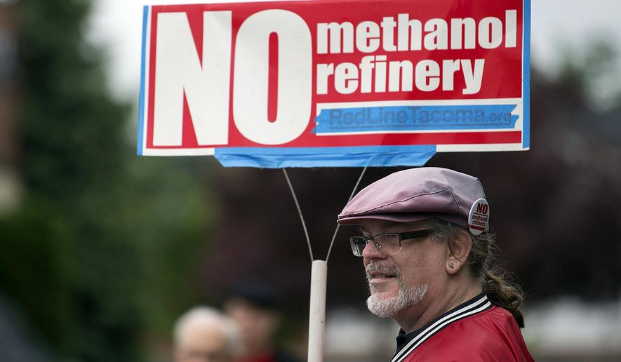 FILE - In this 2017 file photo, Mark Keely, of Kalama, Wash., stands with other protesters outside the Washington Department of Ecology's Vancouver field office in 2017. Keely and others were demonstrating against the proposed methanol refinery that could be built in Kalama. The department dealt the project a setback on Friday, Nov. 22, 2019, saying it could not proceed without further environmental review of its greenhouse gas emissions. (Amanda Cowan/The Columbian via AP, File)