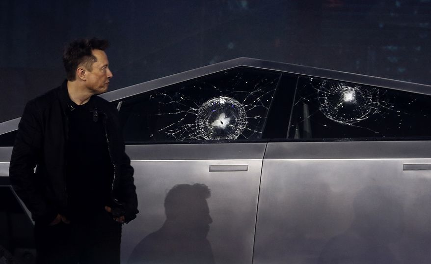 Tesla CEO Elon Musk looks at the broken window glass as he introduces the Cybertruck at Tesla's design studio Thursday, Nov. 21, 2019, in Hawthorne, Calif. Musk is taking on the workhorse heavy pickup truck market with his latest electric vehicle. (AP Photo/Ringo H.W. Chiu)