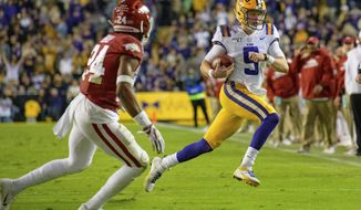 LSU quarterback Joe Burrow (9) runs for a first down, near Arkansas defensive back LaDarrius Bishop (24) during the first half of an NCAA college football game in Baton Rouge, La., Saturday, Nov. 23, 2019. (AP Photo/Matthew Hinton)