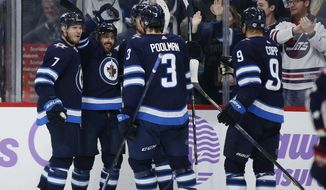 Winnipeg Jets' Dmitry Kulikov (7), Mathieu Perreault (85), Tucker Poolman (3) and Andrew Copp (9) celebrate Perreault's  goal against the Columbus Blue Jackets during the second period of an NHL hockey game, Saturday, Nov. 23, 2019 in Winnipeg, Manitoba. (John Woods/The Canadian Press via AP)