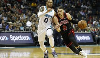 Chicago Bulls' Zach LaVine (8) drives the lane against Charlotte Hornets' Miles Bridges (0) during the second half of an NBA basketball game in Charlotte, N.C., Saturday, Nov. 23, 2019. (AP Photo/Bob Leverone)