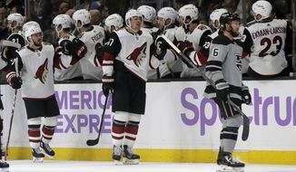 Arizona Coyotes left wing Lawson Crouse, center, celebrates his goal with teammates as Los Angeles Kings defenseman Joakim Ryan, right, makes his way to the Kings' bench during the second period of an NHL hockey game in Los Angeles, Saturday, Nov. 23, 2019. (AP Photo/Alex Gallardo)