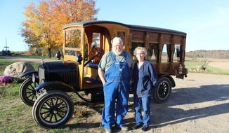 Ted and Diana Hawk stand in front of the 1925 Ford Model TT hearse Ted and his nephew are building, on Oct. 24, 2019, outside the Hawks' home in East Rochester, Ohio. (Rachel Wagoner/Farm and Dairy via AP)