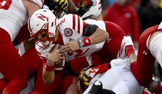 Nebraska quarterback Adrian Martinez (2) runs against Maryland defenders during the first half of an NCAA college football game, Saturday, Nov. 23, 2019, in College Park, Md. (AP Photo/Will Newton)
