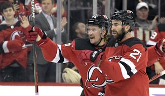 New Jersey Devils center Kyle Palmieri (21) celebrates his goal with New Jersey Devils defenseman Sami Vatanen (45) during the second period of an NHL hockey game against the Detroit Red Wings Saturday, Nov. 23, 2019, in Newark, N.J. (AP Photo/Bill Kostroun)