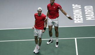 Canada's Denis Shapovalov, left, and his partner Vasek Pospisil celebrate after winning their Davis Cup semifinal doubles match against Russia's Karen Khachanov and Andrey Rublev, in Madrid, Spain, Saturday, Nov. 23, 2019. (AP Photo/Bernat Armangue)