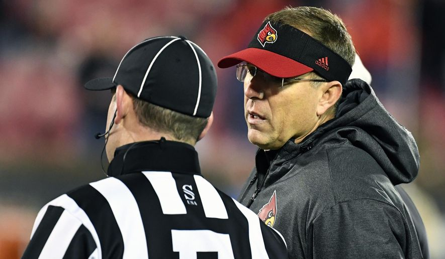 Louisville head coach Scott Satterfield, right, talks with an official during the second half of an NCAA college football game in Louisville, Ky., Saturday, Nov. 23, 2019. (AP Photo/Timothy D. Easley)