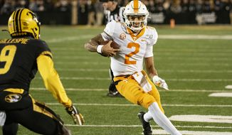 Tennessee quarterback Jarrett Guarantano, right, runs the ball as Missouri safety Tyree Gillespie, left, moves in during the first quarter of an NCAA college football game against Tennessee, Saturday, Nov. 23, 2019, in Columbia, Mo. Tennessee won 24-20. (AP Photo/L.G. Patterson)