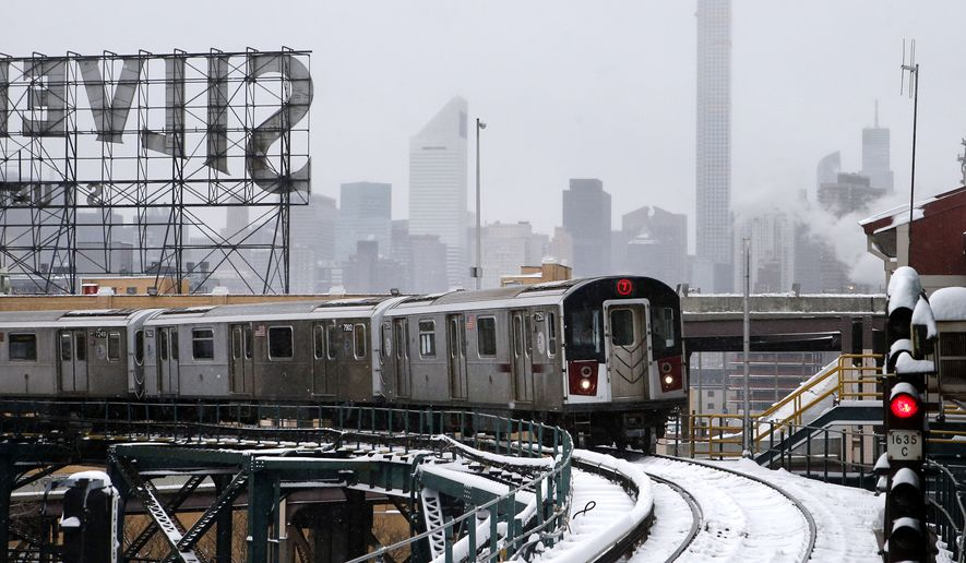 Part of the Manhattan skyline can be seen as a Flushing-bound 7 train arrives at Queensboro Plaza station after limited subway service was restored following a winter storm, Tuesday, Jan. 27, 2015, in the Queens borough of New York. Gov. Andrew Cuomo says a snowstorm-related New York City area travel ban is lifted, except for Suffolk County on Long Island. (AP Photo/Jason DeCrow)