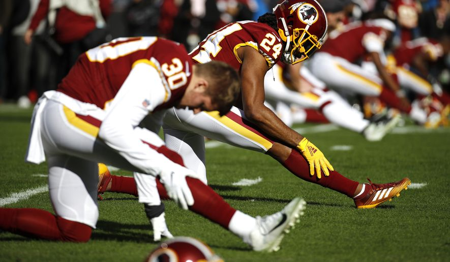 Washington Redskins cornerback Josh Norman (24) and free safety Troy Apke stretch prior to an NFL football game against the Detroit Lions, Sunday, Nov. 24, 2019, in Landover, Md. (AP Photo/Patrick Semansky)
