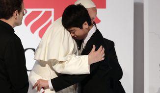 Pope Francis hugs Matsuki Kamoshita as he meets with victims of the March 11, 2011 Fukushima nuclear plant disaster in northern Japan Monday, Nov. 25, 2019, in Tokyo, Japan. (AP Photo/Jae Hong)