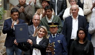 Bolivia's interim President Jeanine Anez, left, poses for a picture after enacting a law to hold new elections in La Paz, Bolivia, Sunday, Nov. 24, 2019. Bolivia is struggling to stabilize after weeks of anti-government protests and violence in which at least 30 people have been killed. Former president Evo Morales resigned on Nov. 10 after an election that the opposition said was rigged. (AP Photo/Juan Karita)