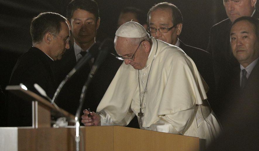 Pope Francis signs a visitors' book at Hiroshima Peace Memorial Park for a meeting in Hiroshima, western Japan, Sunday, Nov. 24, 2019. (AP Photo/Gregorio Borgia)
