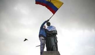 An anti-government demonstrator waves a Colombian flag after he climbed up to a statue of South American independence hero Simon Bolivar during a  protest at Bolivar square in Bogota, Colombia, Sunday, Nov. 24, 2019. Authorities are maintaining a heightened police presence amidst scattered unrest in the aftermath of a mass protest that drew about 250,000 to the streets Thursday. (AP Photo/Ivan Valencia)