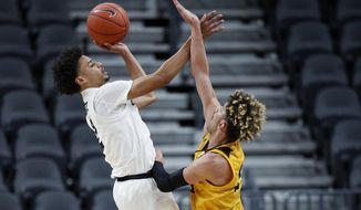 Colorado's Daylen Kountz, left, shoots over Wyoming's Hunter Maldonado, right, during the first half on an NCAA college basketball game Sunday, Nov. 24, 2019, in Las Vegas. (AP Photo/John Locher)