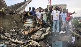 Rescuers and onlookers gather amidst the debris of an aircraft operated by private carrier Busy Bee which crashed in Goma, Congo Sunday, Nov. 24, 2019.  The plane carrying at least 17 passengers crashed Sunday on takeoff in Congo's eastern city of Goma in North Kivu province, killing those on board, officials said, and possibly people on the ground after the aircraft crashed into residential homes. (AP Photo/Justin Kabumba)
