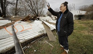 In this photo taken Monday, Nov. 18, 2019, Tammy Kilgore looks over the remains of her home after it was demolished as part of a voluntary buyout in food-prone Mosby, Mo. Kilgore accepted a $45,000 payment to leave her home of 38 years and has moved to a nearby community. (AP Photo/Charlie Riedel)