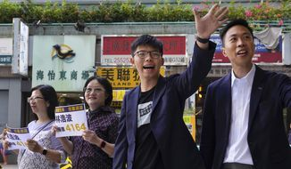 Election winner candidate Kelvin Lam, right, and pro-democracy activist Joshua Wong, second right, wave to people and thank for their support, outside South Horizons Station in Hong Kong, Monday, Nov. 25, 2019. Pro-democracy candidates won nearly half of the seats in Hong Kong's local elections, according to partial returns Monday, as voters sent a clear signal of support for the anti-government protests that rocked the Chinese territory for more than five months. (AP Photo/Vincent Yu)