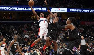 Washington Wizards guard Bradley Beal (3) goes to the basket next to Sacramento Kings guard Buddy Hield (24) and forward Richaun Holmes (22) during the second half of an NBA basketball game, Sunday, Nov. 24, 2019, in Washington. Also seen are Kings forward Harrison Barnes (40) and Wizards forward Rui Hachimura (8). The Kings won 113-106. (AP Photo/Nick Wass)