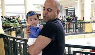 In this June 2016, photo provided by Guila Fakhoury, her father Amer Fakhoury holds his granddaughter, Kira, in King of Prussia, Penn. Amer Fakhoury, a U.S. citizen living in Dover, N.H., went to visit family in his native Lebanon in September after a 20-year absence, and has been jailed there by authorities since. (Guila Fakhoury via AP)