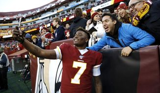 Washington Redskins quarterback Dwayne Haskins takes selfies with fans during the second half of an NFL football game against the Detroit Lions, Sunday, Nov. 24, 2019, in Landover, Md. The Redskins won 19-16. (AP Photo/Patrick Semansky) ** FILE **