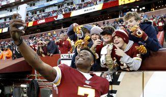 Washington Redskins quarterback Dwayne Haskins takes selfies with fans during the second half of an NFL football game against the Detroit Lions, Sunday, Nov. 24, 2019, in Landover, Md. The Redskins won 19-16. (AP Photo/Patrick Semansky) **FILE**
