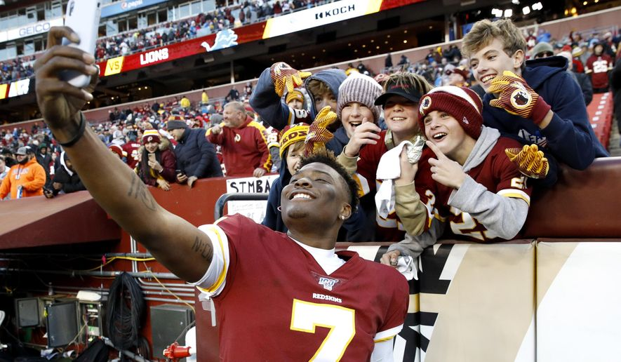 Washington Redskins quarterback Dwayne Haskins takes selfies with fans during the second half of an NFL football game against the Detroit Lions, Sunday, Nov. 24, 2019, in Landover, Md. The Redskins won 19-16. (AP Photo/Patrick Semansky) **FILE**