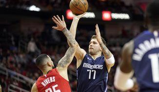 Dallas Mavericks' Luka Doncic (77) shoots as Houston Rockets' Austin Rivers (25) defends during the first half of an NBA basketball game Sunday, Nov. 24, 2019, in Houston. (AP Photo/David J. Phillip)