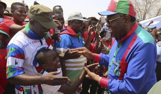 Namibian President Hage Geingob, right, greets supporters at an election rally in Grootfontein, Namibia, Thursday, Nov. 21, 2019. Namibia votes Wednesday in an election that promises to be far removed from the overwhelming victories enjoyed by former liberation movement SWAPO since independence in 1990. (AP Photo/Sonja Smith)