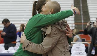 Oregon's Sabrina Ionescu, left, and Syracuse's Tiana Mangakahia, right, embrace before an NCAA basketball game in Syracuse, N.Y., Sunday, Nov. 24, 2019. Mangakahia was diagnosed with Stage 2 breast cancer and is not expected to play this season. (AP Photo/Nick Lisi)