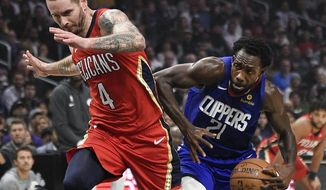 Los Angeles Clippers guard Patrick Beverley, right, pushes off on New Orleans Pelicans guard JJ Redick while driving to the basket resulting in an offensive foul during the first half of an NBA basketball game in Los Angeles, Sunday, Nov. 24, 2019. (AP Photo/Kelvin Kuo)