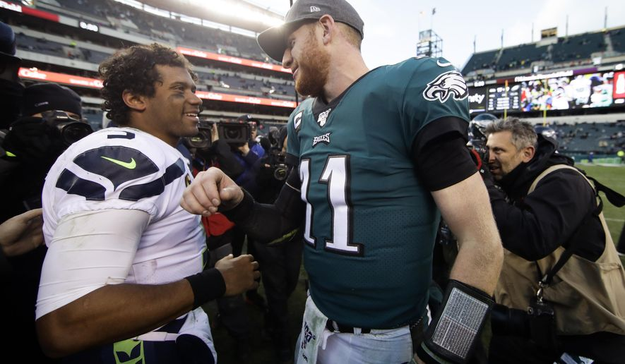 Seattle Seahawks' Russell Wilson, left, and Philadelphia Eagles' Carson Wentz meet after an NFL football game, Sunday, Nov. 24, 2019, in Philadelphia. Seattle won 17-9. (AP Photo/Matt Rourke)