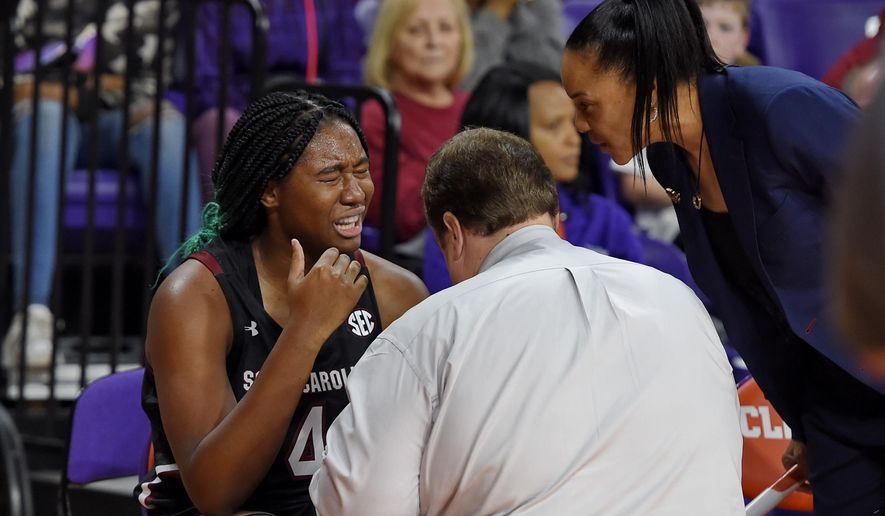 South Carolina head coach Dawn Staley, right, checks on Aliyah Boston while a trainer tends to Boston after an injury during the first half of an NCAA college basketball game against Clemson, Sunday, Nov. 24, 2019, in Clemson, S.C. (AP Photo/Richard Shiro)