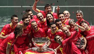 Spain's Rafael Nadal, foreground, takes a selfie with fellow players and team staff posing with the trophy after Spain defeated Canada 2-0 to win the Davis Cup final in Madrid, Spain, Sunday, Nov. 24, 2019. (AP Photo/Bernat Armangue)