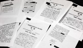 A sample of classified Chinese government documents leaked to a consortium of news organizations, is displayed for a picture in New York, Friday, Nov. 22, 2019. Beijing has detained more than a million Uighurs, ethnic Kazakhs and other Muslim minorities for what it calls voluntary job training. The confidential documents lay out the Chinese government's deliberate strategy to lock up ethnic minorities to rewire their thoughts and even the language they speak. (AP Photo/Richard Drew)