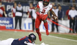 Utah running back Zack Moss (2) avoids the tackle attempt by Arizona defensive lineman Trevon Mason during the first half during an NCAA college football game Saturday, Nov. 23, 2019, in Tucson, Ariz. (AP Photo/Rick Scuteri)