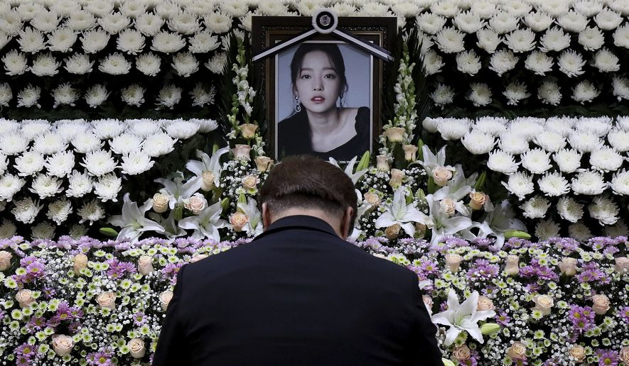 A South Korean man pays tribute to K-pop star Goo Hara at a memorial altar at the Seoul St. Mary's Hospital in Seoul, Monday, Nov. 25, 2019. Hara was found dead at her home in Seoul on Sunday, police said. (Chung Sung-Jun/Pool Photo via AP)