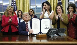 President Donald Trump displays the Women's Suffrage Centennial Commemorative Coin Act after signing it during a ceremony in the Oval Office of the White House, Monday, Nov. 25, 2019, in Washington. (AP Photo/Patrick Semansky)